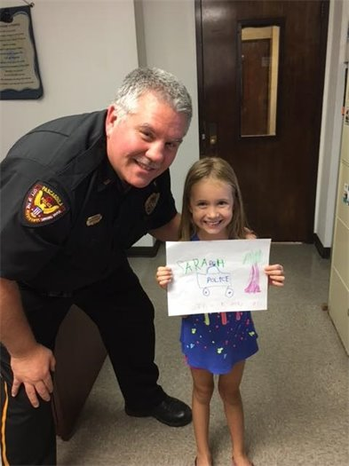 Police Officer with a child her drawing