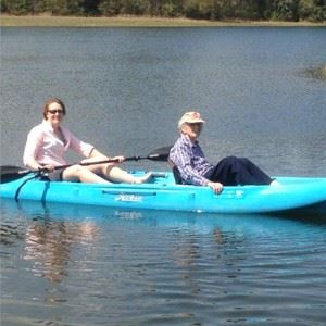 Image of two passengers in  a teal kayak