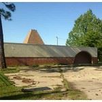 Image of brick one story building with pyramidal structure on top and a grassy parking lot