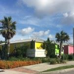 Image of three small one story buildings, one yellow, one green, one pink, with palm trees and a sid