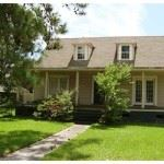 Two story creamy yellow colored home, with a small sidewalk leading to front door and large grass fr