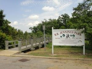 B.B. Jennings Park sign beside wooden footbridge in forest